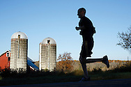 Goshen, New York  - A runner races past a barn and silos in the Hambletonian Marathon on Sunday, Oct. 20, 2013.