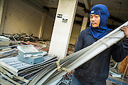 "11 DECEMBER 2012 - BANGKOK, THAILAND:  A worker takes out window blinds from a building being torn down at ""Washington Square"" a notorious entertainment district off Sukhumvit Soi 22 in Bangkok. Demolition workers on many projects in Thailand live on their job site tearing down the building and recycling what can recycled as they do so until the site is no longer inhabitable. They sleep on the floors in the buildings or sometimes in tents, cooking on gas or charcoal stoves working from morning till dark. Sometimes families live and work together, other times just men. Washington Square was one of Bangkok's oldest red light districts. It was closed early 2012 and is being torn down to make way for redevelopment.    PHOTO BY JACK KURTZ"