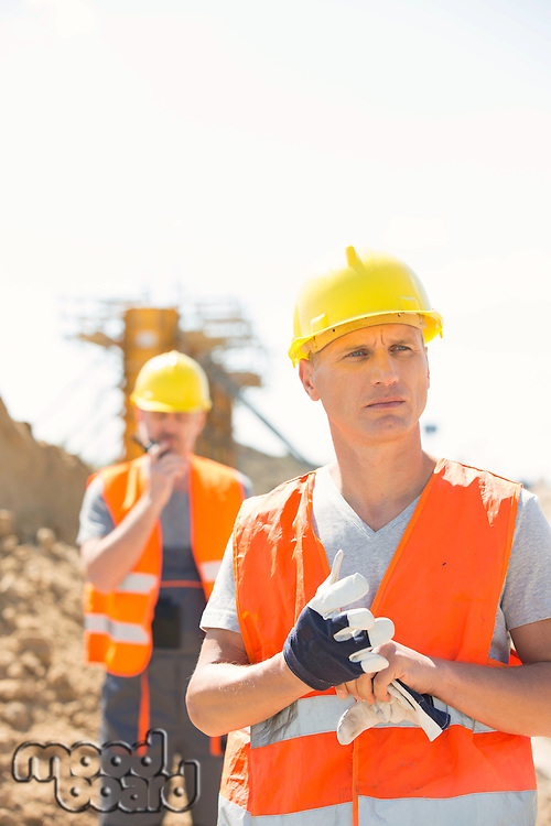 Male worker standing at construction site with colleague in background