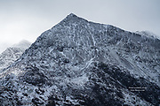 Three imposing sharp peaks of Yr Wyddfa (Snowdon) in the cold glow of winter light.