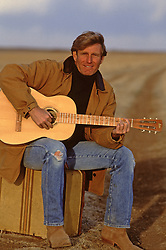 Handsome man playing the guitar while sitting on a suitcase in a field