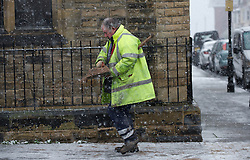 © Licensed to London News Pictures. 14/01/2013..Saltburn, Cleveland, England..A council worker spreads grit onto slippery pavements as the snow falls in Saltburn.  ..Photo credit : Ian Forsyth/LNP