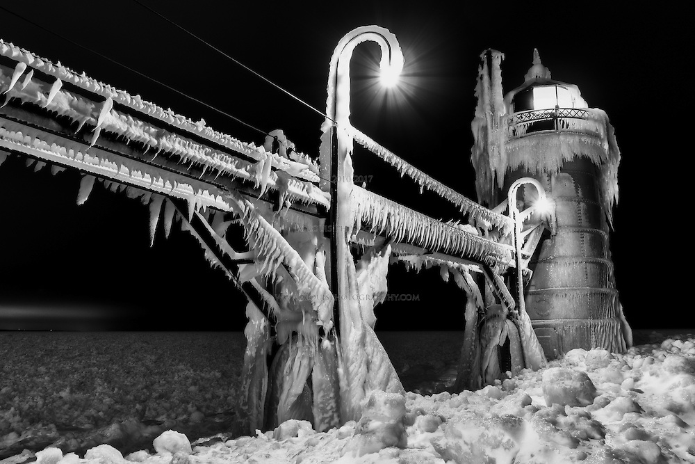 The lighthouse of South Haven, Mi stands watch over the frozen Lake Michigan shoreline.