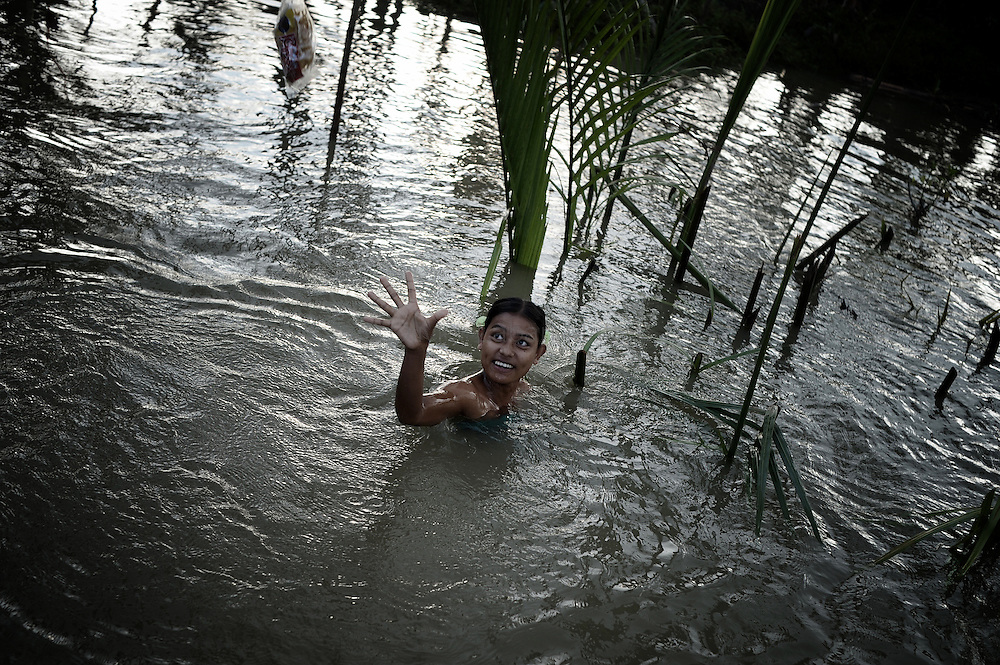 A young woman puts her hand up to receive food thrown from a boat by locals on May 23, 2008 in the isolated area of Kanzeik in the Irrawaddy Delta region -- an area only accessible by boat which has received neither government nor foreign aid. Voters in regions devastated by the cyclone, many hungry and destitute, cast ballots on May 24 in a referendum that many said was meaningless because Myanmar's junta has already declared victory.