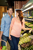 Happy young couple looking at each other while shopping for vegetables in market