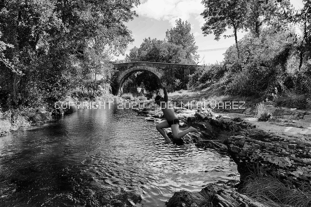 A kid jumps in the river Neira with a roman brigde in the background, in the area where a canadian company want to open a pit gold mine using cyanid. . Val de Neira, Lugo