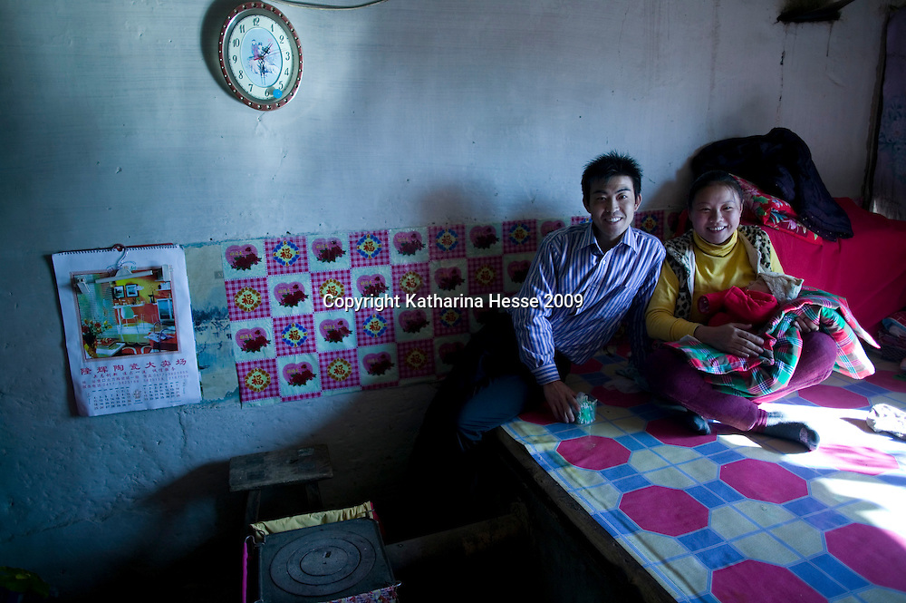 NORTHERN HEBEI PROVINCE, JANUARY 26, 2009:<br /> Mr Lu, a textile worker in Beijing, celebrates Chinese New Year with his wife and newborn in his parents' home in Hebei province, near the border to Inner Mongolia.<br /> Lu went to Beijing 8 years ago as he couldn't find a job in China's countryside.<br /> He was employed in a textile factory that went banctrupt last October. Lu and his 63 colleagues were still owed payment for 4 months, but their boss refused to pay them. They didn't know the law, nor did any of them have a contract.  <br /> At the end of January, Lu and his co-workers went to see the bosses' mother to negociate, then the union and in the end the government. They were threatened with jail . At the end of the day , a man from the union came by ( on behalf of the government )and all but an underaged worker received their due salaries.<br /> Now Lu is unemployed like 20 milion other migrant workers in China who have been laid off as a result of the financial crisis.<br /> <br /> <br /> China's Communist Party  which will celebrate its 60th anniversary in October, currently faces its biggest challenge since the beginning of the economic reforms 30 years ago  : &quot; The phase of  rapid economic growth is over. For the first time the government is threatened with a  mistrust of a wide section of the population&quot;, warns the Communist party's Shang Dewen in Beijing.   <br /> Not only the China's poorest worry about the furture, but as well China's middle class is concerned about the crisis.     1,5 Millionen university graduates didn't find a job until the end of 2008  and this summer there'll be an additional  6,1 Million new graduates. More than 12 percent of university graduates face unemployment in 2009.
