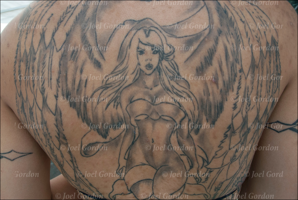 Close up of winged female nude covering her whole back.<br /> <br /> Body art or tattoos has entered the mainstream it is known longer considered a weird kind of subculture.<br /> <br /> Tattoos are no longer just a male thing, young women are just as likely to get a tattoo as males.<br /> <br /> &quot;According to a 2006 Pew survey, 40% of Americans between the ages of 26 and 40 have been tattooed&quot;.