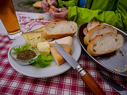 Person eating cheese and baguette meal on table, Vosges, France
