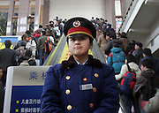 A young woman monitors travelers inside the Beijing train station during the holiday travel rush.