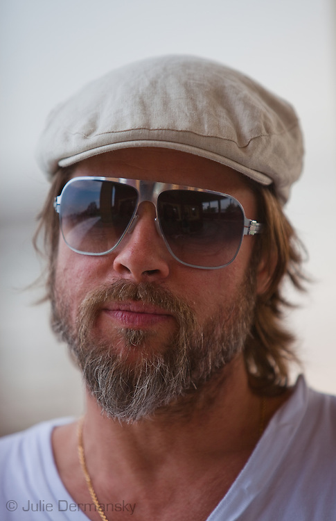 """Brad Pitt wearing a beard and a berret on the deck of one of the homes in  his """"Make it Right"""" housing project in New Orleans Lower 9th Ward that was devestated by Hurricane Katrina."""