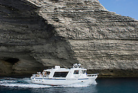 France: Corsica, Bonifacio, limestone coastline, one of the boats that cross to and from the Lavezzi Islands (which lie c. 10 km South East) exiting a cave