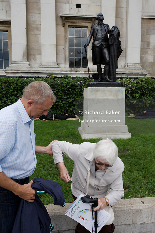 An elderly lady is helped up from a sitting position near the statue of US President George Washington in London's Trafalgar Square. It might be a relative who holds the frail woman by her left arm as she struggles to get upright, despite the use of a walking stick. On the brochure she is holding, is the text relating to the upcoming 2012 Olympics. The statue of George Washington is a replica of a work by Jean-Antoine Houdon, to the north east corner of the Square that commemorates the Battle of Trafalgar (1805), a British naval victory of the Napoleonic Wars over France.
