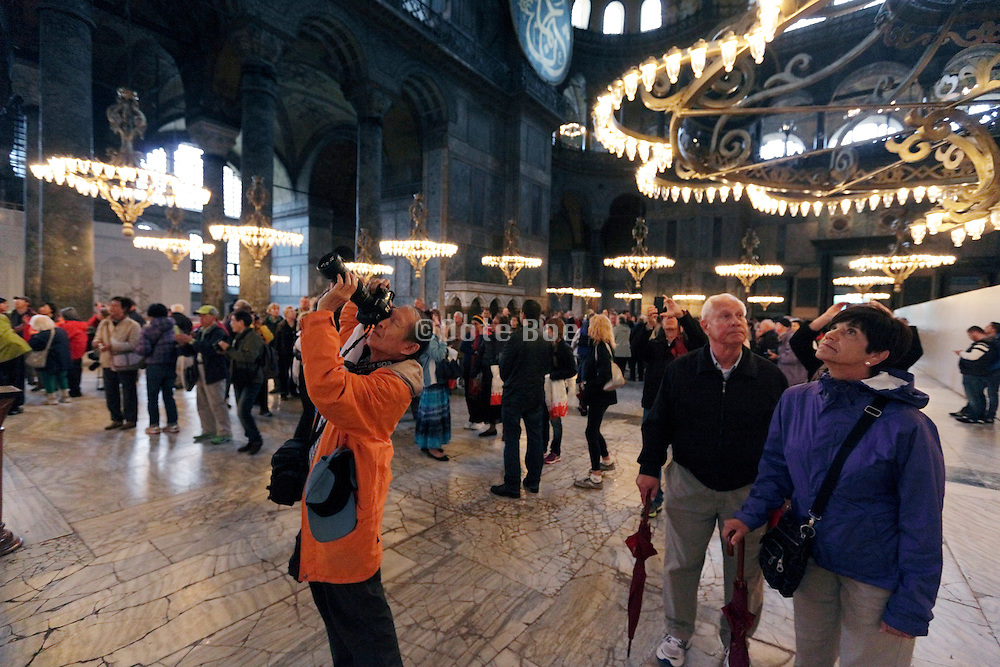 tourists looking up in the very large Hagia Sophia Museum Mosque Istanbul Turkey