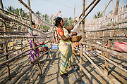 Local women hang fish on long racks to dry them in the sun. This area is famous for its dried fish.