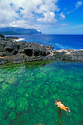 Girl diving into Queen's Bath near Princeville (Na Pali Coast visible), North Shore, Island of Kauai, Hawaii