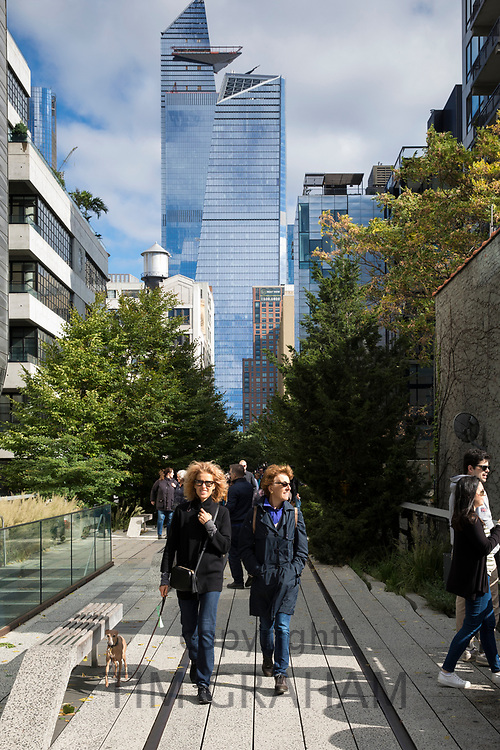 Tourists and disused train tracks on The High Line elevated park walkway and high rise skyscrapers on west side Manhattan, New York City