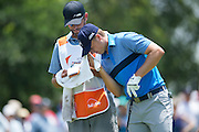 Jordan Spieth and his caddy, Michael Greller, check yardage from the fairway during the first round of the AT&T Byron Nelson in Las Colinas, Texas on May 28, 2015. (Cooper Neill for The New York Times)