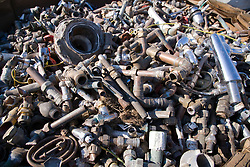 Pile of Copper tube with brass fittings waiting to be sorted at metal recycling centre,