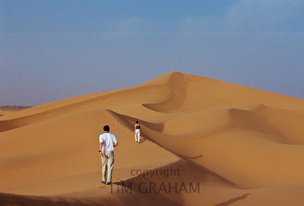 Tourists climbing a sand dune in the Sahara Desert, Morocco.