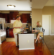 Model released couple in high rise apartment talking and enjoying company.