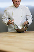 Male chef mixing ingredients using whisk in kitchen