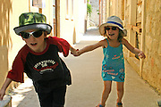 2 children boy aged 6 and girl aged 4 with hats and sunglasses in a small alley in Ston, Croatia