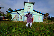 Man with machete clears field in front of church in Garifuna village of Barranco, in southern Belize.