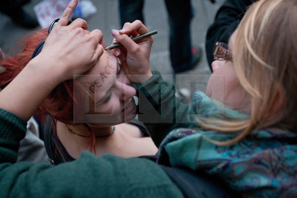 © licensed to London News Pictures. London, UK 12/05/2012. An Occupy London protester writing ''Peaceful'' on another protesters forehead as the protesters occupy the area outside the Bank of England, this evening (12/05/12). Photo credit: Tolga Akmen/LNP