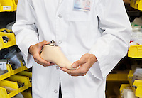 Mid section of a young technician holding artificial foot