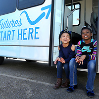 Zaria Bell, 9, of Tupelo, and Chloee Green, 9, of Plantersville, pass the time as they sit on the steps of the Boys & Girls Club new 24 passenger bus that was purchased with  a grant received last year from the ER Carpenter Foundation. The group made a small field trip to the Carpenter Company to thank them for the donation.