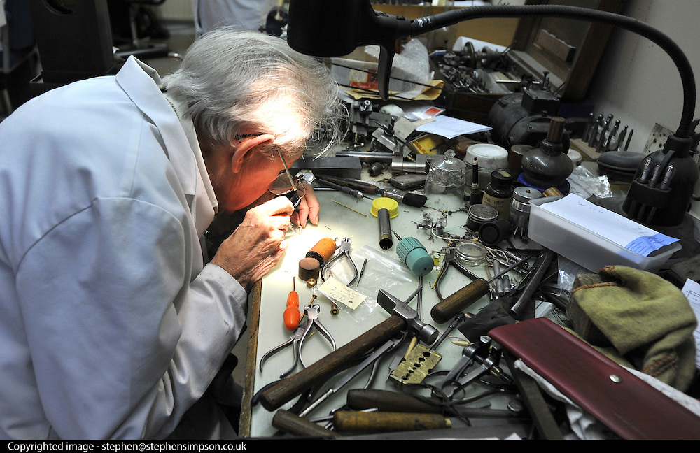 """©London News pictures...28/10/2010.  Dudley Taylor, 76, a clockmaker all his life, working at his desk. Staff at Horological Workshops start the task of changing the 100's of clocks at their store in Guildford, Surrey, UK. Micahel Tooke who has owned the store for 43 years and worked in the clock business all his life said. """"at this time of year we get alot of people who bring clocks in for repair after they have changed the time incorreectly by winding back the hands manually"""""""