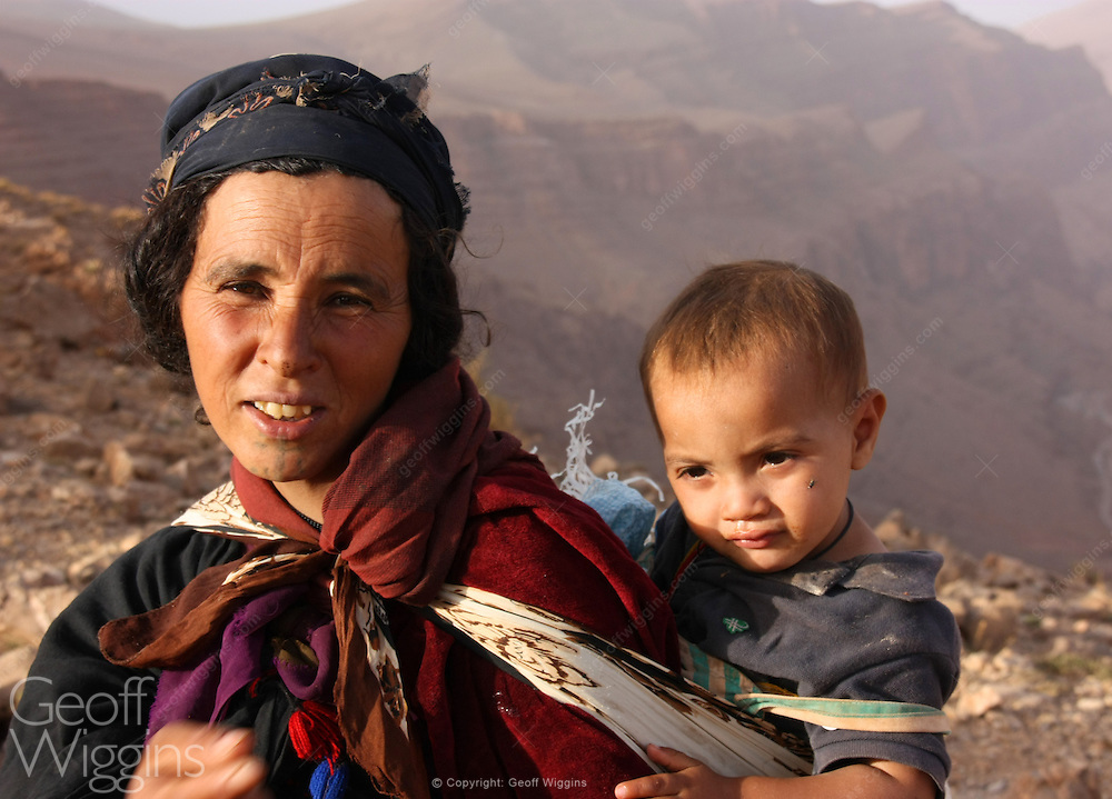 Nomad Berber woman and child in traditional clothing high in the Atlas Mountains Morocco