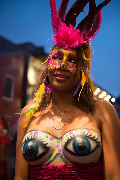A beautiful woman at Mardi Gras, a mask and plummage on her head and blue eyes painted over her breasts, stands on Bourbon Street in New Orleans, Louisiana.