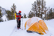 Backcountry skier and snow-covered dome tent, John Muir Wilderness, Sierra Nevada Mountains, California  USA