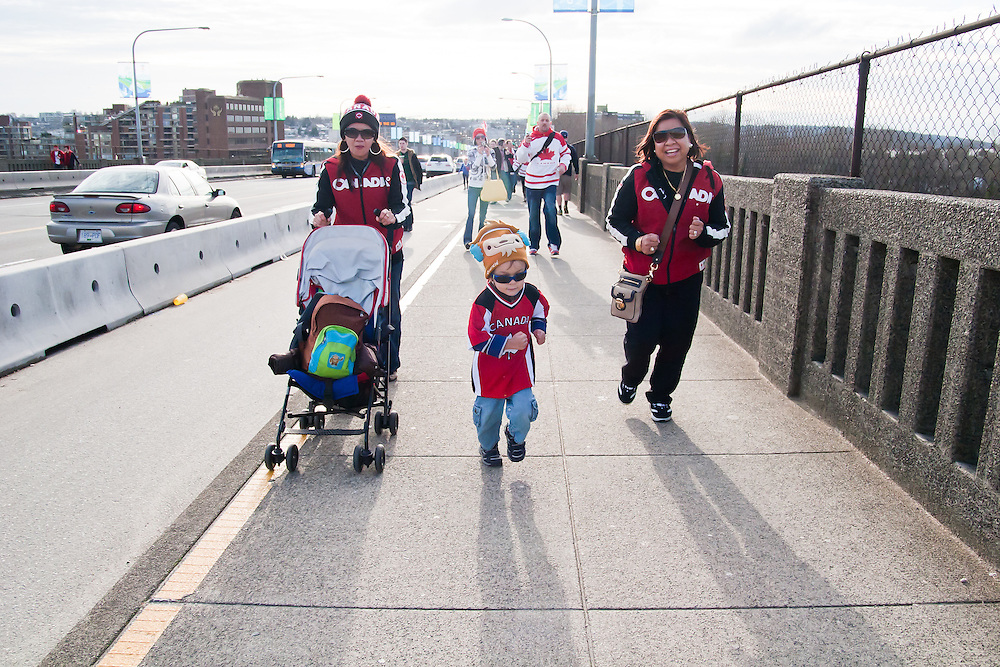A young boy runs down the sidewalk on Burrard Bridge, eager to get to the celebrations taking place downtown.<br /> <br /> Tens of thousands of people in Vancouver took to the streets on Sunday 28th February 2010 to celebrate Canada's 3-2 overtime win over the United States for the gold medal in men's Olympic hockey...Traffic came to a halt in and around the downtown of the host city for the Winter Games following the dramatic finish to the match, which featured Sidney Crosby scoring to secure the victory on the final day of Olympic competition.