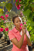 Woman Smelling a Flower at a Nursery