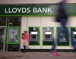 © Licensed to London News Pictures. 26/10/2016. Portsmouth, UK.  People walking past the Portsmouth branch of Lloyds Bank. The bank, 9pc-owned by the taxpayer, have set aside a further £1billion to cover claims over the mis-selling of Payment Protection Insurance (PPI). The announcement has come on the day the bank has reported that statutory pre-tax profits for the three months to the end of September fell 15% to £811m.  Photo credit: Rob Arnold/LNP