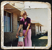 mother posing with child in front of the house
