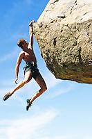 Young man hanging from rock outcrop. Joshua Tree National Park, California, USA