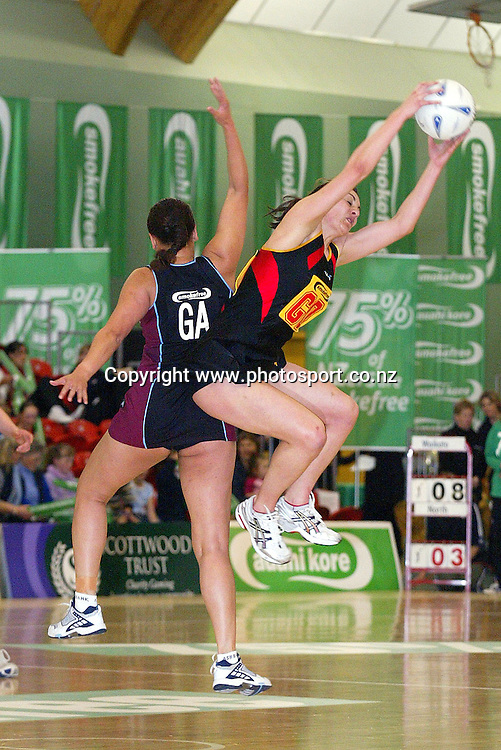 Waikato's Joline Henry takes a pass with Netball North's Teresa Tairi in Defence during Waikato's 63-43 win over Netball Ball North at the Smokefree NPC Div 1 final on Saturday night. Arena Manawatu, Palmerston North, 25 September 2004.<br /> Photo:Marty Melville/Photosport