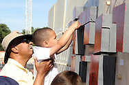 "James Nalls helps Tyler, 6, place a block with a personal message on the ""Better Wall"" during the All Pro Dad Father & Kids NFL Experience at Welcome Stadium, Saturday, June 18, 2016."