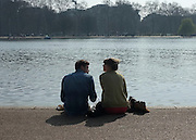© Licensed to London News Pictures. 24/03/2012. London, UK. A young couple sit on the banks of the Serpentine Lake. People enjoy the warm sunshine today 24 March 2012 in Hyde Park Central London . Photo credit : Stephen SImpson/LNP