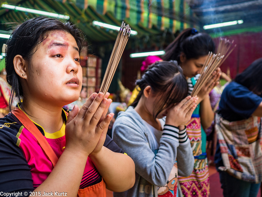 "21 DECEMBER 2015 - BANGKOK, THAILAND:  People pray during the rededication of a community Buddhist shrine in Pak Khlong Talat, also called the Flower Market. The market has been a Bangkok landmark for more than 50 years and is the largest wholesale flower market in Bangkok. A recent renovation resulted in many stalls being closed to make room for chain restaurants to attract tourists. Now Bangkok city officials are threatening to evict sidewalk vendors who line the outside of the market. Evicting the sidewalk vendors is a part of a citywide effort to ""clean up"" Bangkok.      PHOTO BY JACK KURTZ"