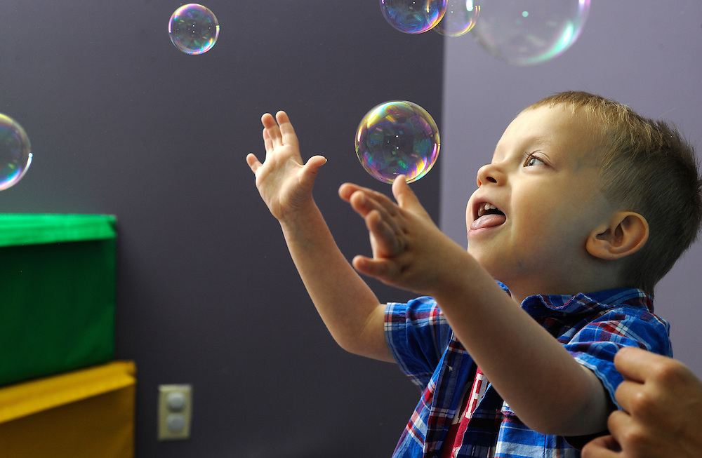 Abyl Chastain, 4, of Viola, Ark.,catches bubbles during a physical therapy session.
