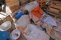 Young boy and small baby asleep on sacks of of farm produce in the weekly bazaar in twn of Mulga in Southwestern Turkey.