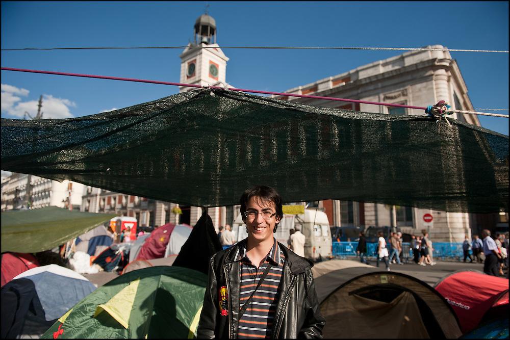 """Robin est Francais, il vient passer le week end sur le camp pour preter main forte et vivre cette experience de l'interieur. Il dort et travaille sur le camp. // Le mouvement spontane du """"15 M"""" (15 mai) compose de citoyens espagnols campe depuis 2 semaines sur la place Puerta Del Sol avec pour revendication la construction d'une democratie nouvelle. Organise en commission les citoyens prennent la parole lors d'assemblee ouverte a tous - Place Puerta Del Sol à Madrid le Juin 2011. ©Benjamin Girette/IP3Press"""