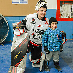 GEORGETOWN, ON - FEBRUARY 2: Goaltender Nathan Torchia #35 of the Georgetown Raiders poses with a young fan on February 2, 2019 at Gordon Alcott Memorial Arena in Georgetown, Ontario, Canada.<br /> (Photo by Michelle Malvaso / OJHL Images)