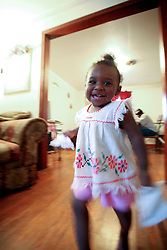 09 July 2006. New Orleans. Louisiana. <br /> Finding Faith. <br /> Faith Figueroa. A day in the life of. Faith runs around the living room on a rainy Sunday afternoon.<br /> Following a ten month search for the little girl whose face appeared on the Sept 19th, 2005 cover of Newsweek magazine, Faith's mother, Miriam Figueroa has returned to town with her three children. Faith, (1 yrs), Anfernya (5yrs) and Jacquelyn (13 yrs). <br /> Credit; Charlie Varley/varleypix.com