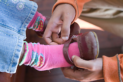 Little boy putting on little sister's shoes for her,